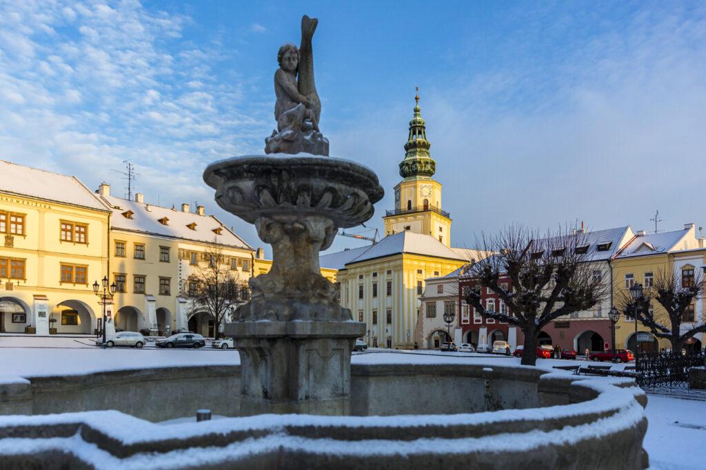 Zasněžená kašna na Velkém náměstí, v pozadí zámecká věž