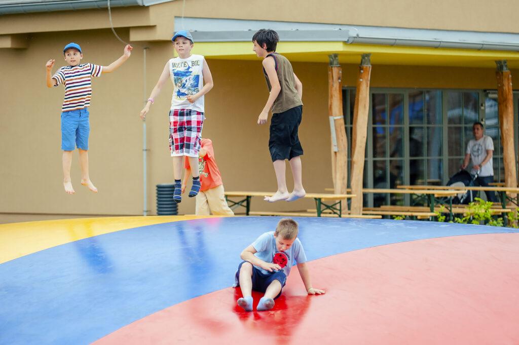Děti skákající na venkovní trampolíně
