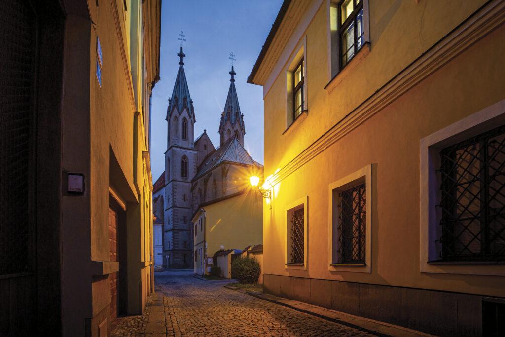 Osvětlená večerní ulice s pohledem na kostel svatého Mořice