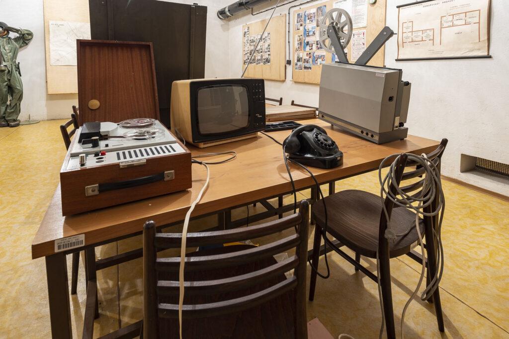 Dobová elektronika umístěná na psacím stole v protiatomovém krytu