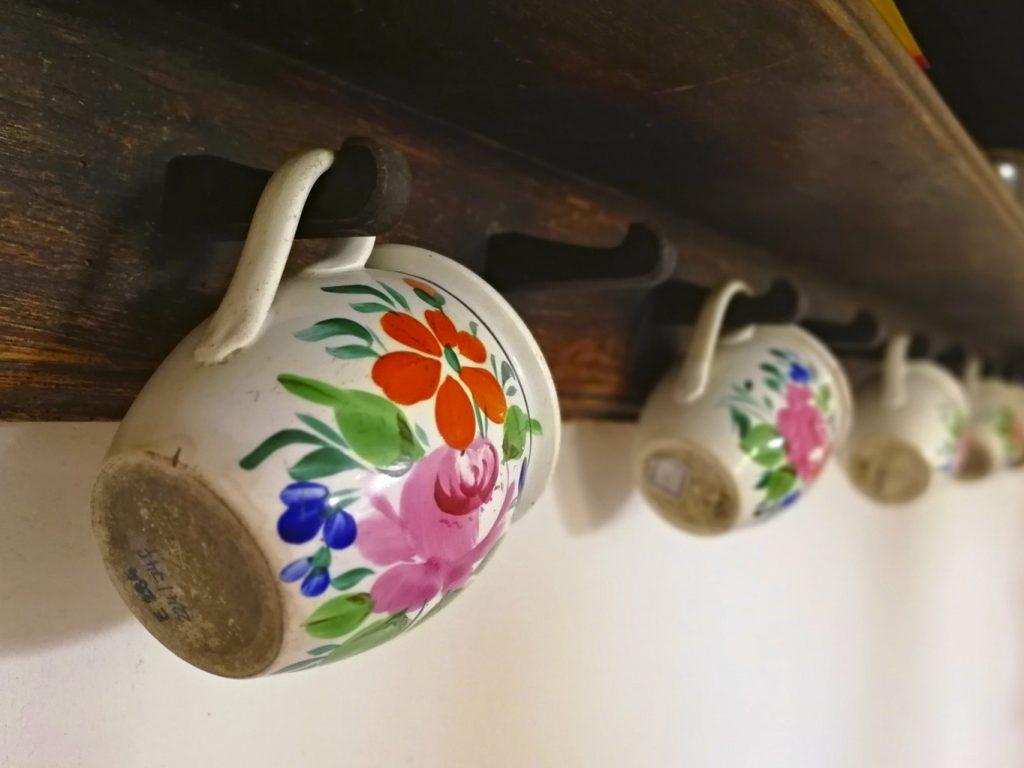 Malované hrnečky s květinovým motivem pověšené na polici