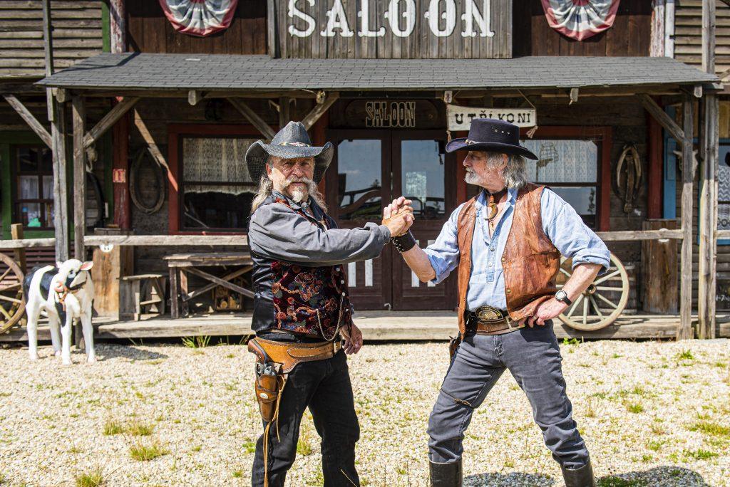Dva kovbojové před salonem ve westernovém městečku