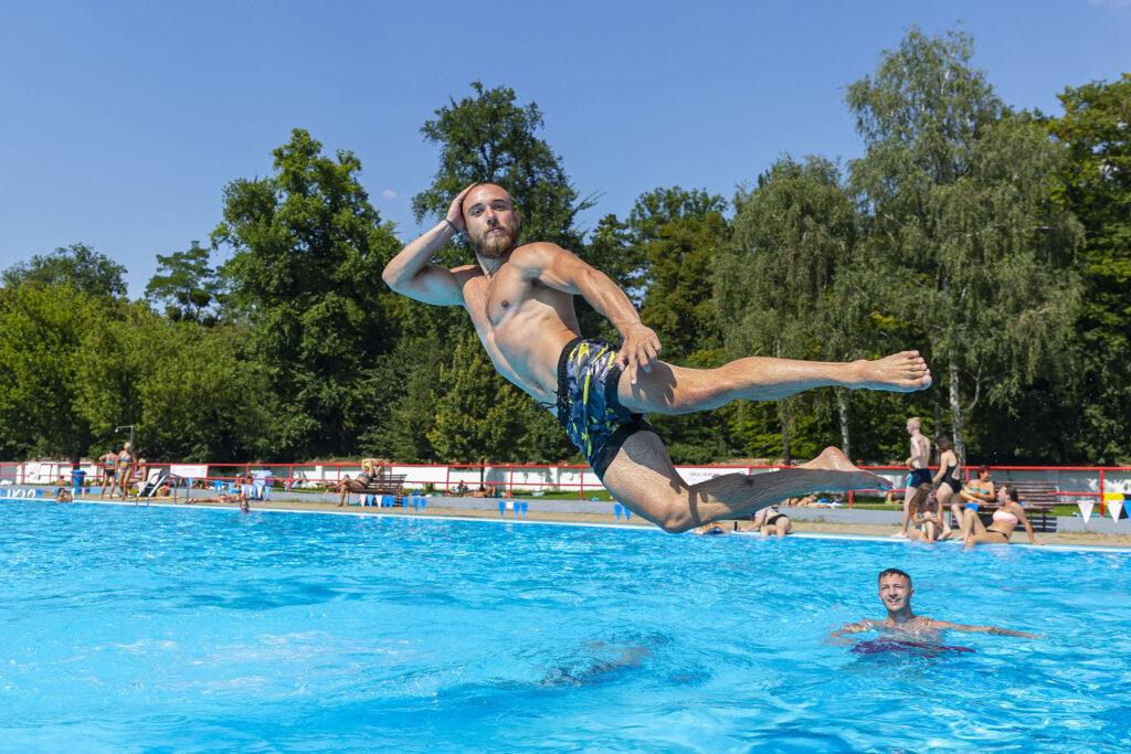 Mladí lidé, skákající do bazénu na koupališti Bajda