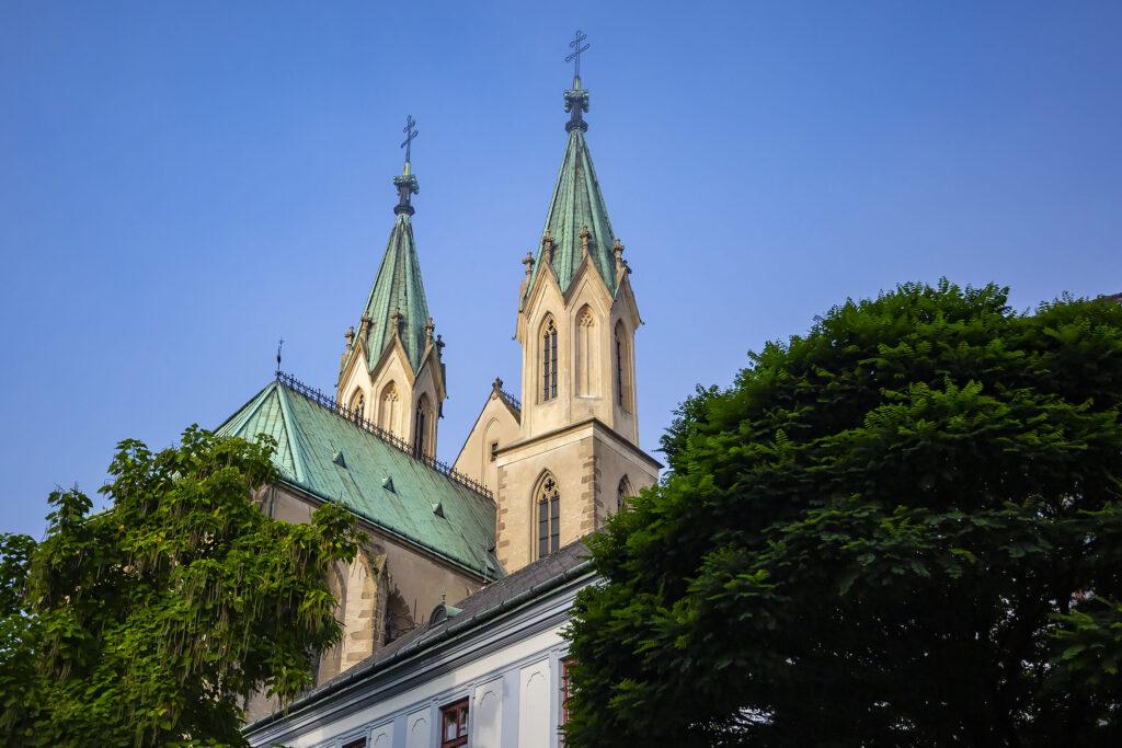 Pohled na věže kostela svatého Mořice mezi korunami stromů