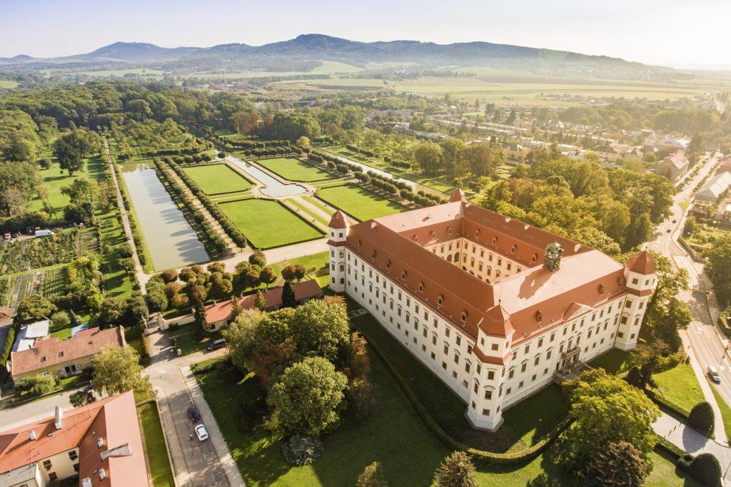 Letecký pohled na holešovský zámek s rozsáhlým zámeckým parkem a Hostýnskými vrchy v pozadí