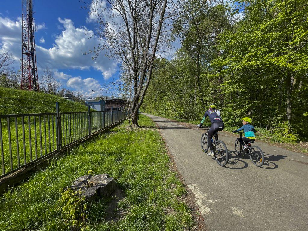 Cyklisté jedoucí po stezce lesoparkem Barbořina