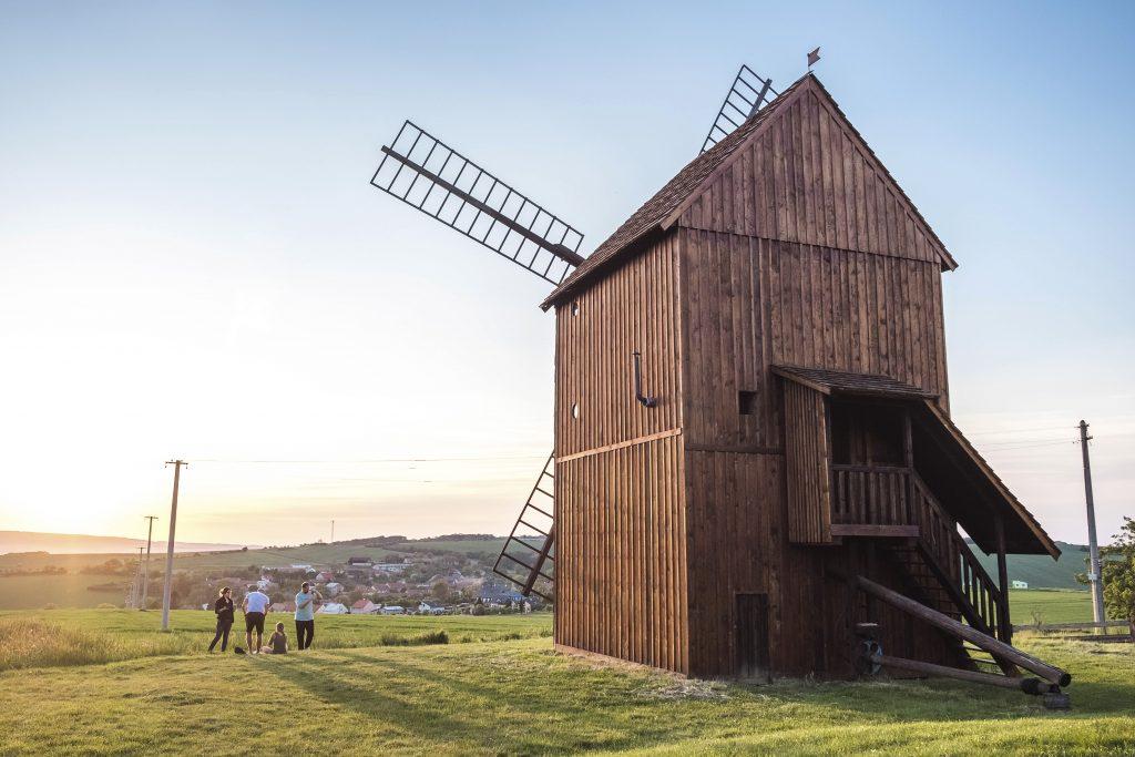 Turisté fotící si větrný mlýn při západu slunce