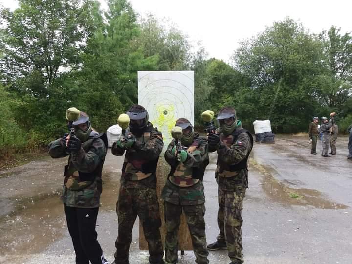 Čtyři účastníci paintballu s vybavením a zbraněmi
