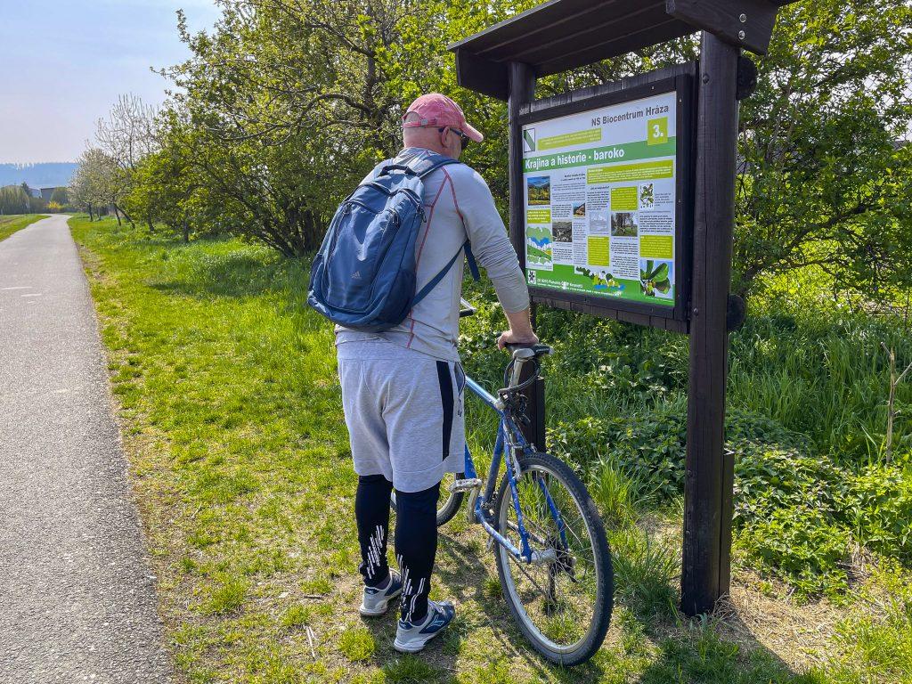 Cyklista prohlížející si naučnou tabuli