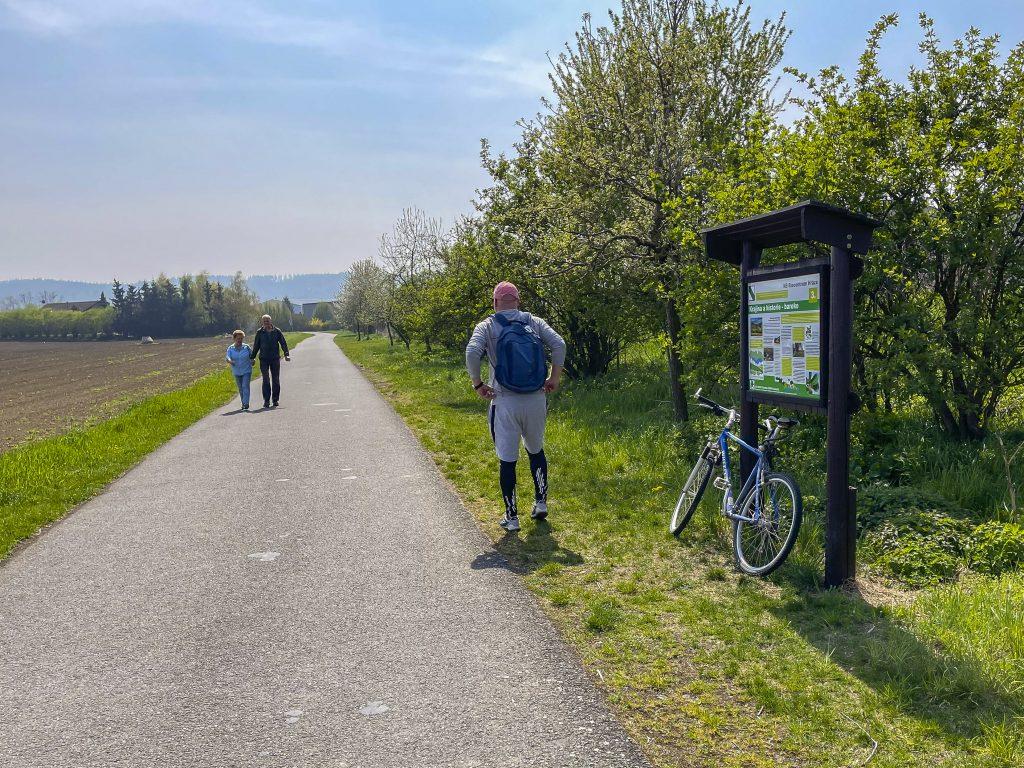 Cyklista a pěší turisté u naučné tabule