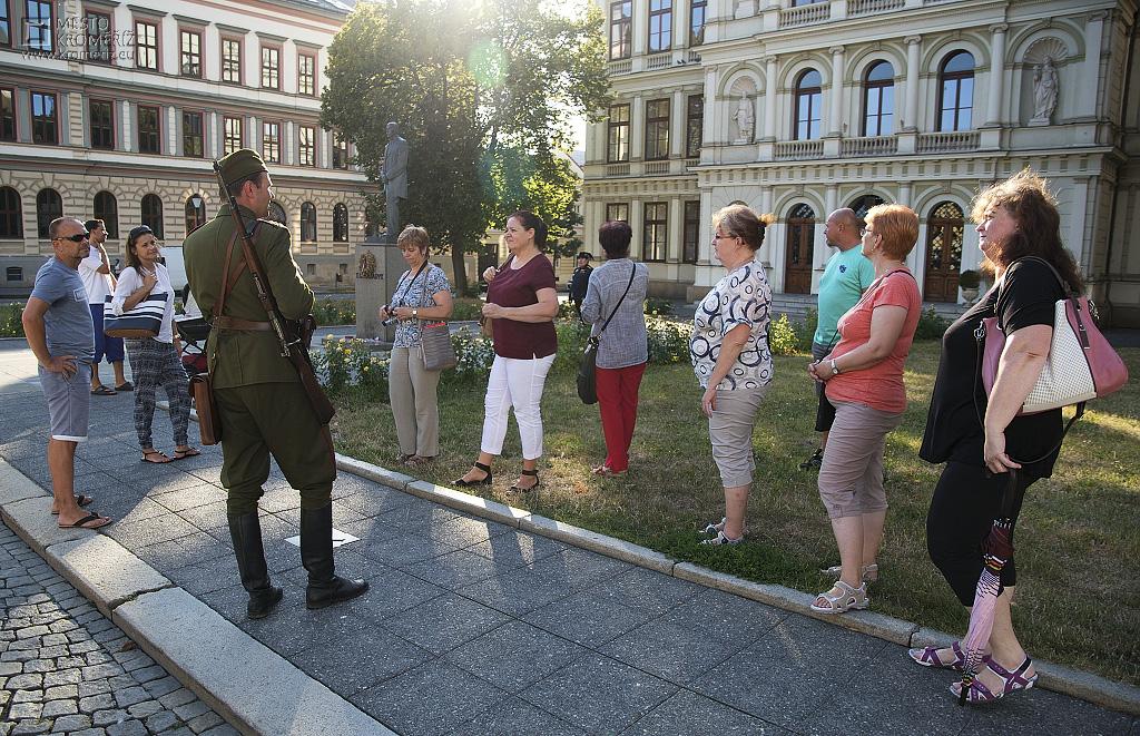 Turisté poslouchající výklad kostýmovaného průvodce před Justiční školou