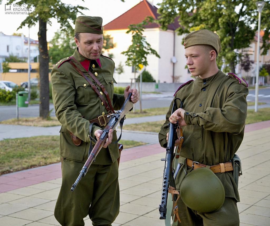 Dva muži v historických uniformách předvádí dobové zbraně