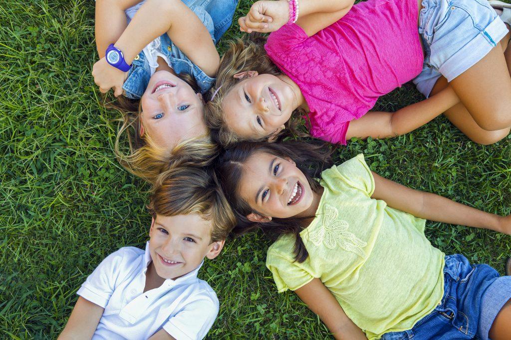 Čtyři děti ležící na trávě