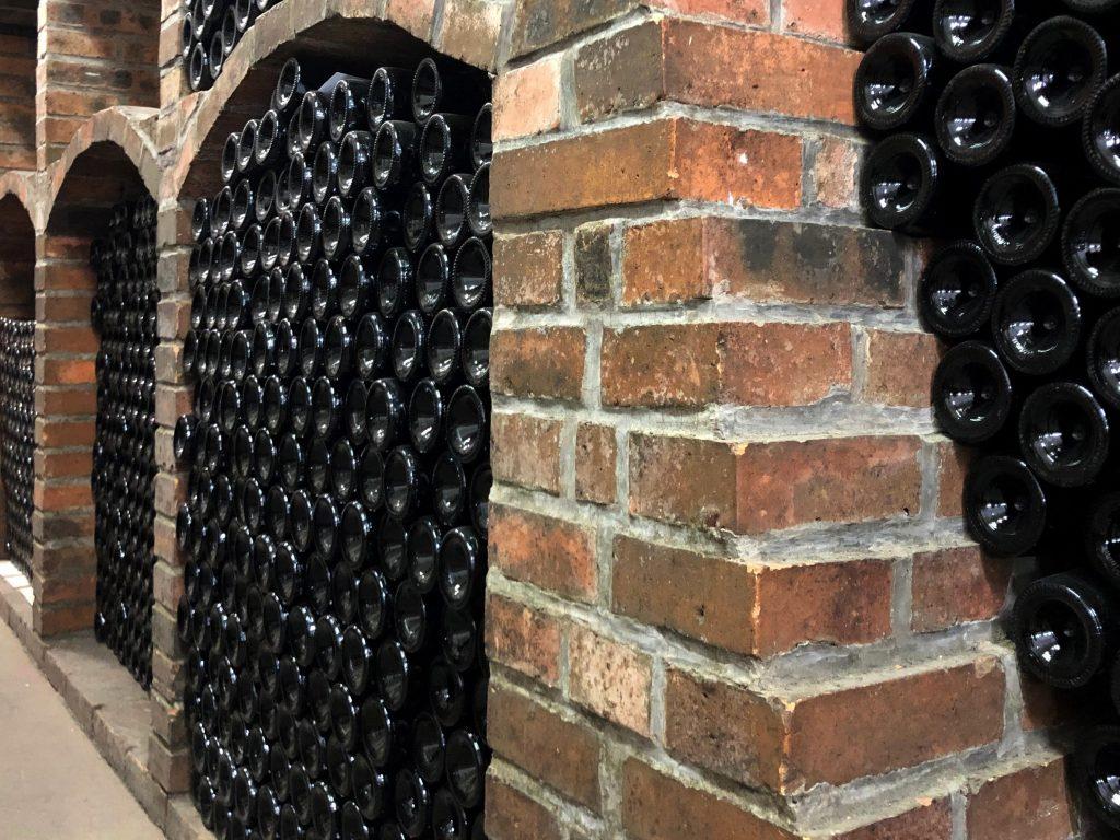 Stovky lahví naskládané na sebe v interiérech vinných sklepů