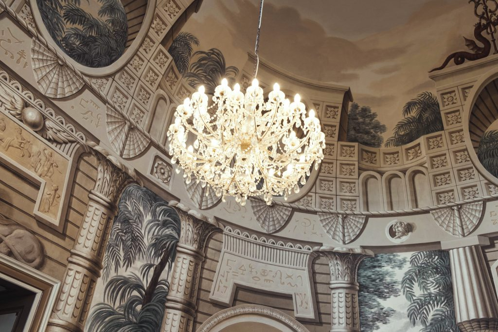 Detail stropu s křišťálovým lustrem a exotickou výmalbou