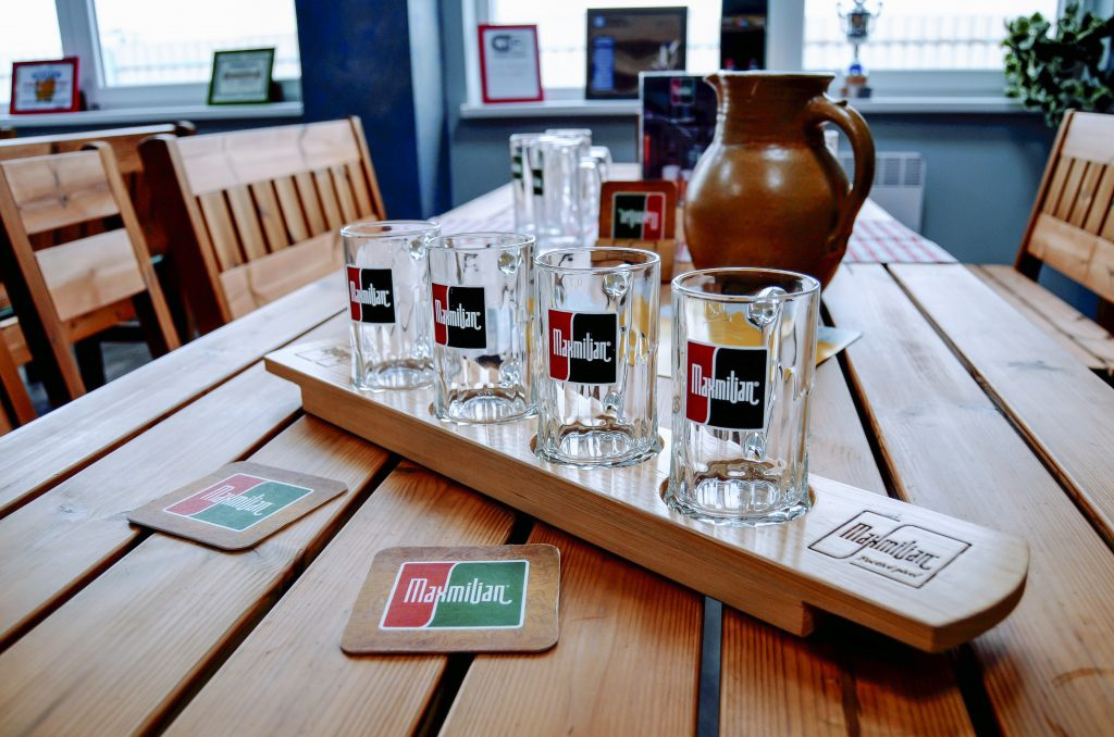 Čtyři půllitry na pivo Maxmilian na dřevěném tácu stejné značky